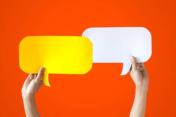 Hands Holding Yellow & White Speech Bubbles Over Orange Background - foto de acervo