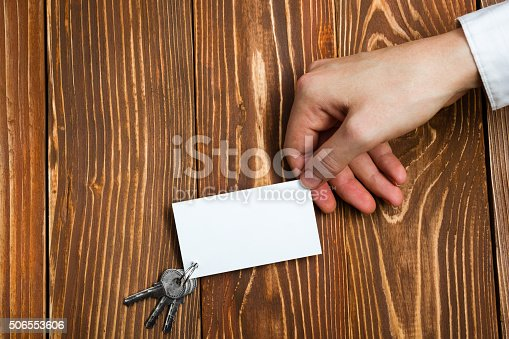 istock Hands holdingblank business card on wooden background. Real Estate. 506553606