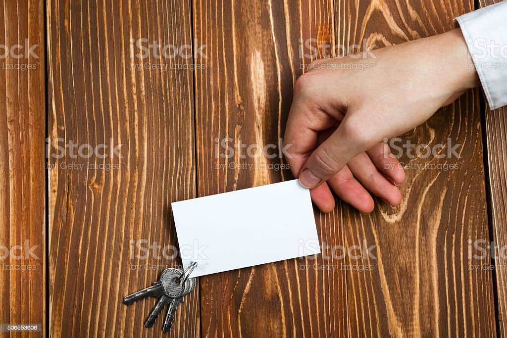 Hands holdingblank business card on wooden background. Real Estate. stock photo