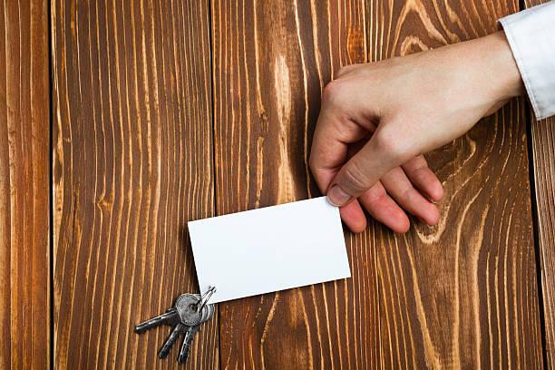 Mãos holdingblank cartão de visita em fundo de madeira. Imóveis. - foto de acervo
