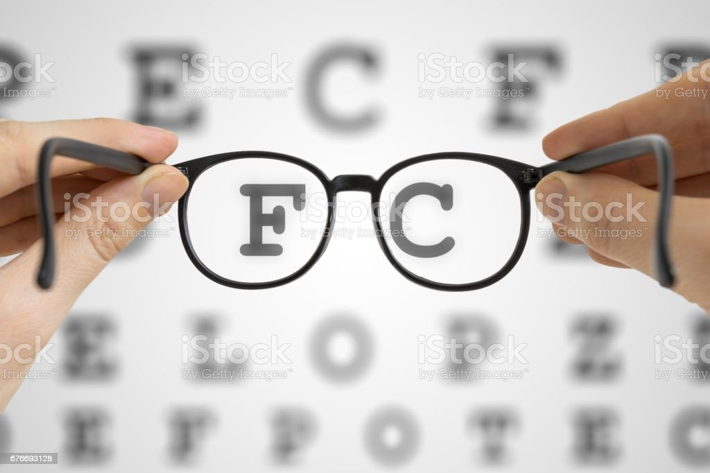 Hands Holds Black Glasses In Front Of Vision Testing Chart Eye Sight