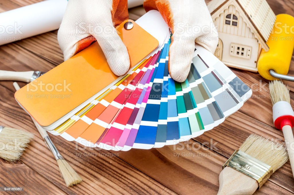 Hands holds color swatches book over table with work tools and model of house. Home improvement and repairing concept. stock photo