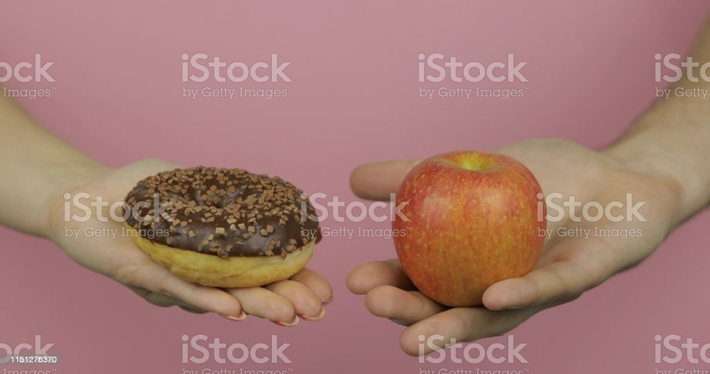 Choice donut against apple. Starting healthy eating or junk food....