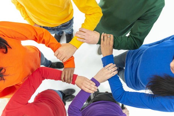 Hands in a circle symbolizing gay pride People in brightly coloured sweaters, representing the gay pride flag, place their hands in a circle formation. cisgender stock pictures, royalty-free photos & images