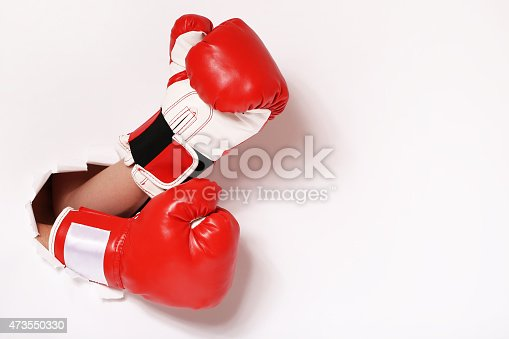 160558362 istock photo Hands in boxing gloves through paper hole 473550330