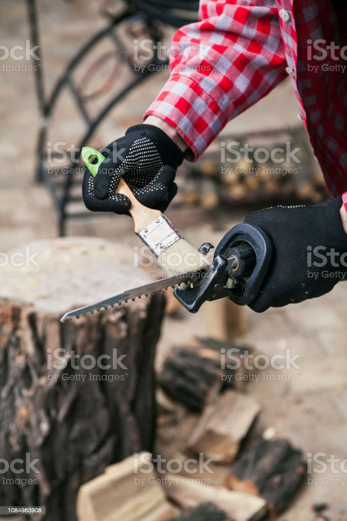 Tool cleaning from sawdust. Hands in a red checked shirt and gloves...