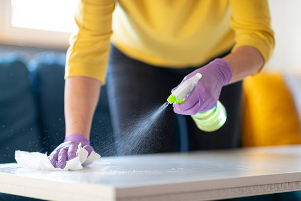 Hands in gloves disinfecting coffee table stock photo