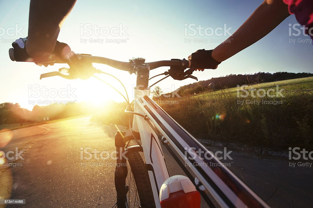 Hands in gloves holding handlebar of a bicycle. stock photo