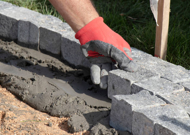 Hands in gloves of a builder worker paving with the granite cobblestone sett  on sand and mortar