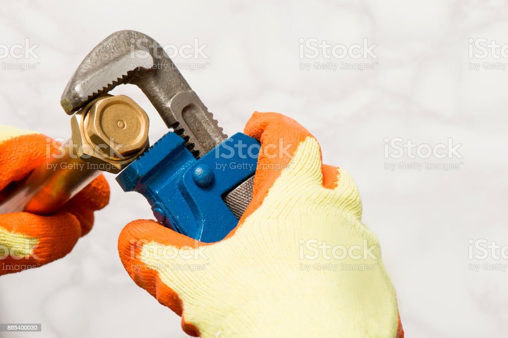 Hands in Gloves Turning a Nut with a Pipe Wrench stock photo