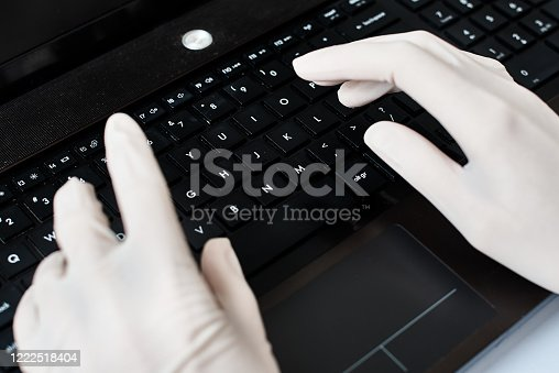 Hands in gloves typing on laptop keyboard. Virus protection concept