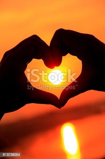 Hands in heart shape framing sunset