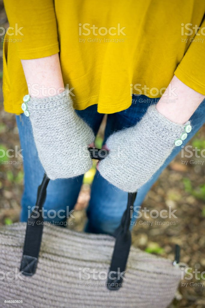 Hands in Knitted Gloves Holding a Woolen Hand Bag stock photo