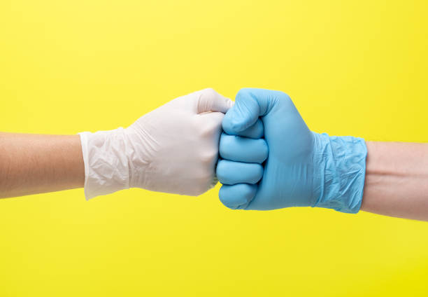 hands in latex medical gloves on a yellow background stock photo
