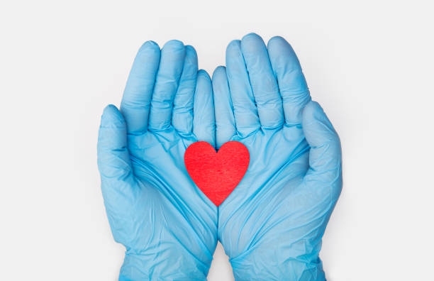 Hands in medical gloves holding a red heart shape stock photo