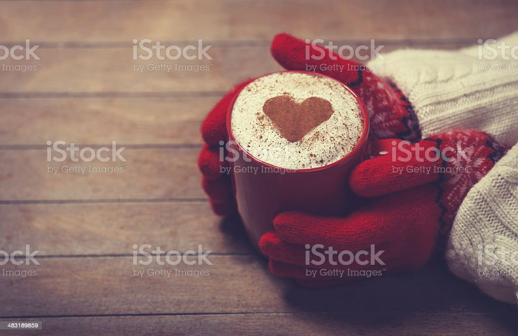 Hands in mittens holding hot cup of coffee stock photo