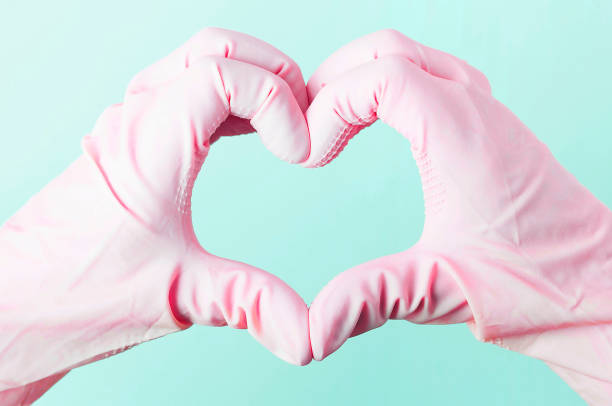 Hands in pink rubber gloves in the shape of a heart on a blue background stock photo