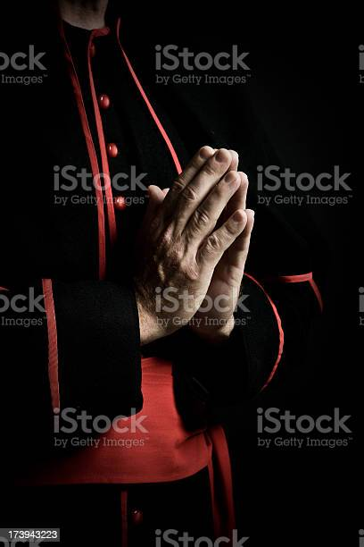 Priest holding a cross in his clasped hands during prayer.