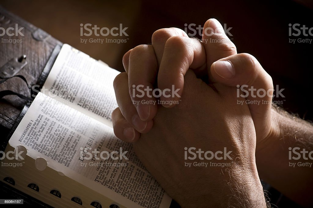 Hands in prayer with open Bible stock photo