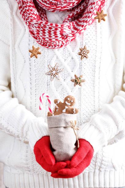 hände in rote handschuhe halten eine tasche mit lebkuchen weihnachtsgebäck und zuckerstange - schal mit sternen stock-fotos und bilder