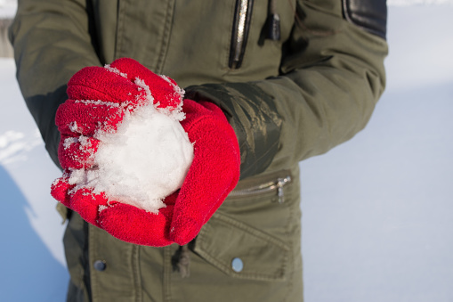 hands in red gloves holding snowball