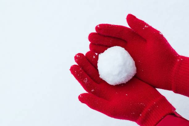 Hands in red gloves holding snowball stock photo
