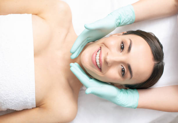 Hands in rubber gloves carefully touching the face of smiling woman stock photo