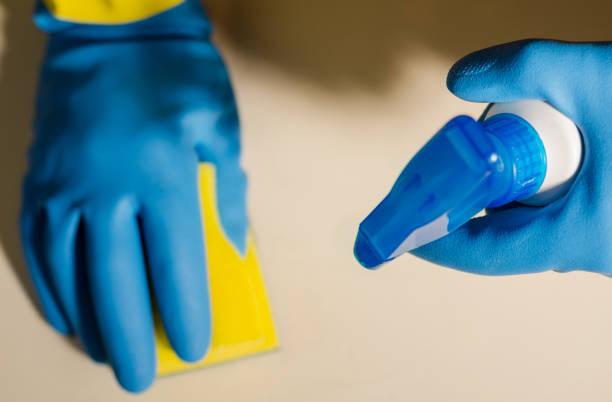 as mãos em luvas de borracha, limpar as superfícies de telhas cerâmicas, segura e higiênica de limpeza - foto de acervo