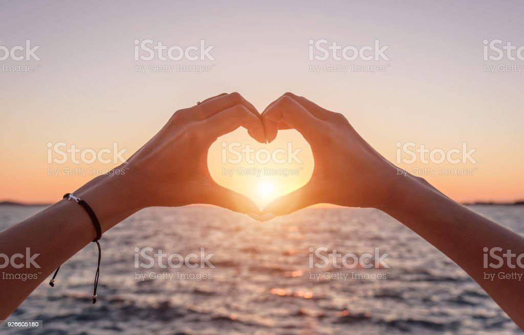 Hands in the shape of a heart at sunset and against the background of the sea.
