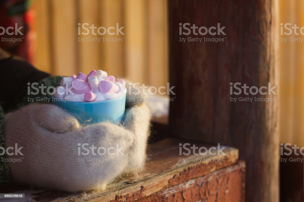 hands in woolen mittens hold blue mug of drink with whipped cream and marshmallows stock photo