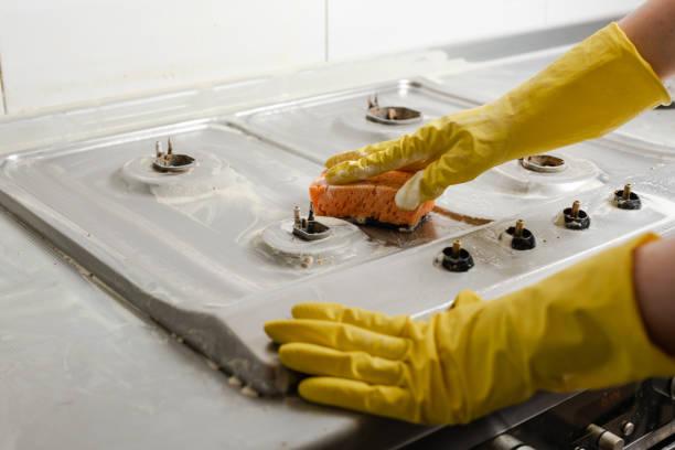 mains en gants jaunes laver le poêle à gaz. - cuisinière photos et images de collection