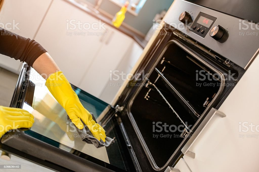 hands in yellow protective rubber gloves cleaning oven stock photo
