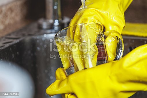 Washing dishes. Hands in yellow rubber gloves wash a glass transparent cup under running water in a metal sink close-up