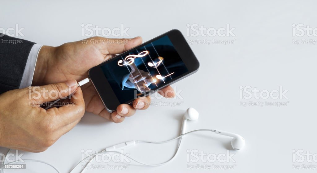 Hands insert earphone jack to smartphone with music on screen, white background stock photo