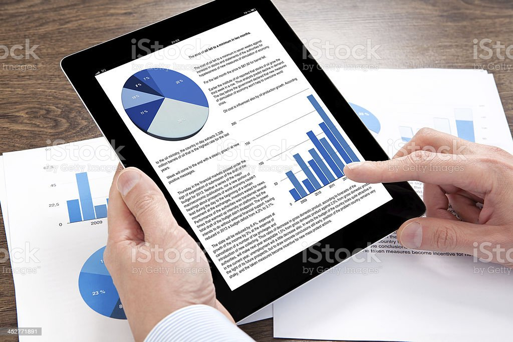 Hands interacting with tablet showing graphs and charts stock photo
