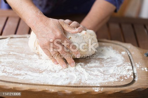 Preparation for making bread: hands of a woman kneading dough on woooden bard, covered with flour