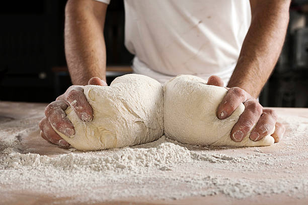 Hands kneading dough  kneading dough stock pictures, royalty-free photos & images
