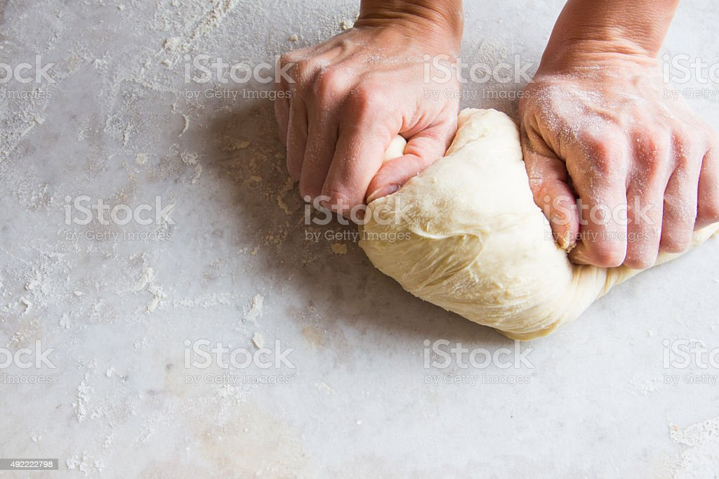 Hands kneading dough stock photo