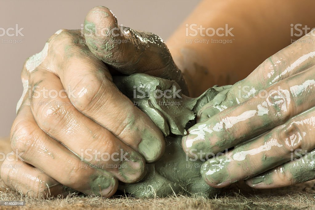 hands kneading raw blue clay stock photo