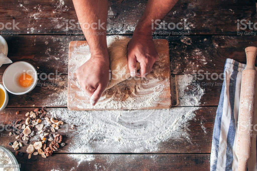 Hands kneading raw dough on table flat lay stock photo