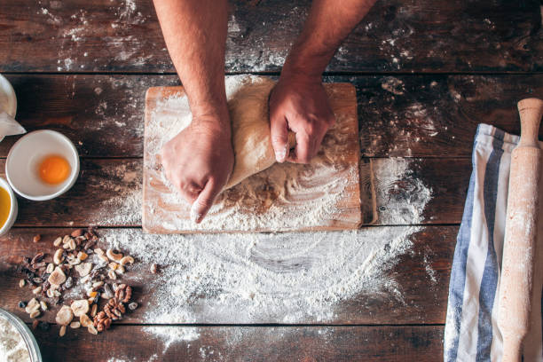 Hands kneading raw dough on table flat lay Hands kneading raw dough on table flat lay. Top view on baker workplace, working with pastry, free space on flowered table. Culinary, cooking, bakery concept baking bread stock pictures, royalty-free photos & images