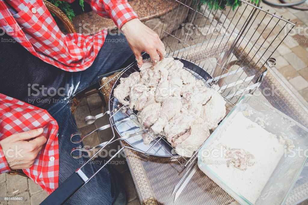 Hands lay pieces of meat in barbecue grill stock photo