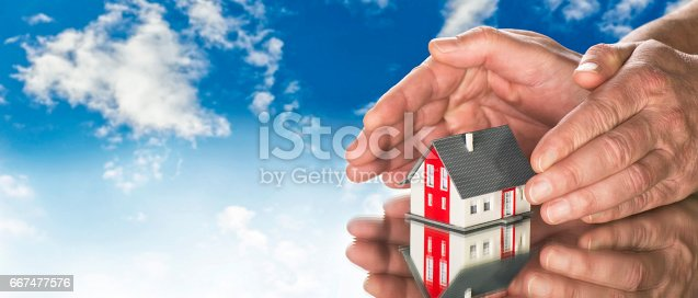 House with hands and blue sky in background