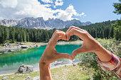 Human hands making heart shape finger frame on lake Carezza in Alto Adige region, Italy.