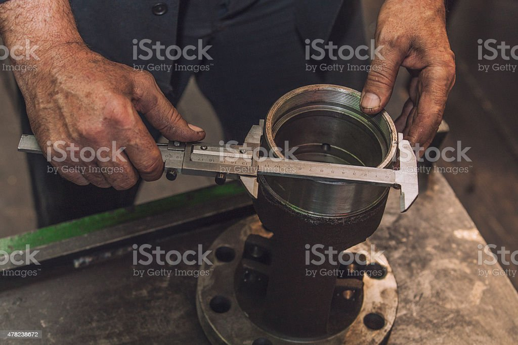 Hands making a measurement with calipers stock photo