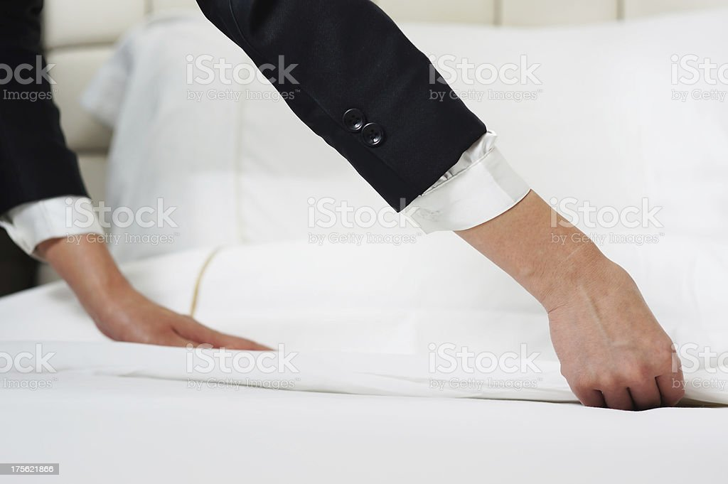 Hands making bed with white sheets royalty-free stock photo