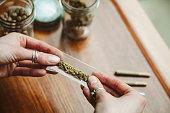 Hands making cannabis joint at marijuana shop