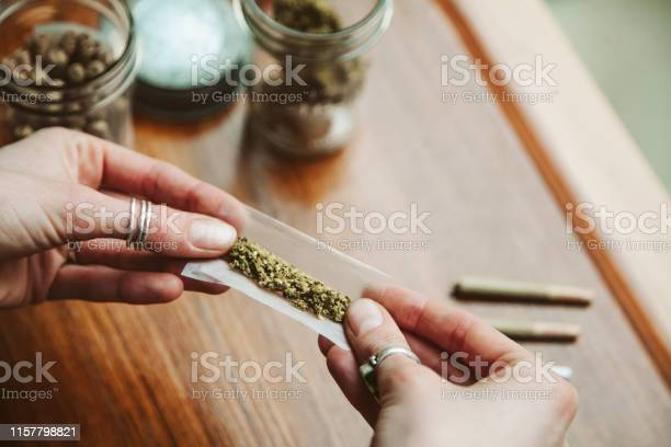 Hands Making Cannabis Joint At Marijuana Shop Stock Photo - Download Image Now