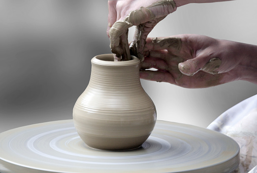 hands making ceramic cup
