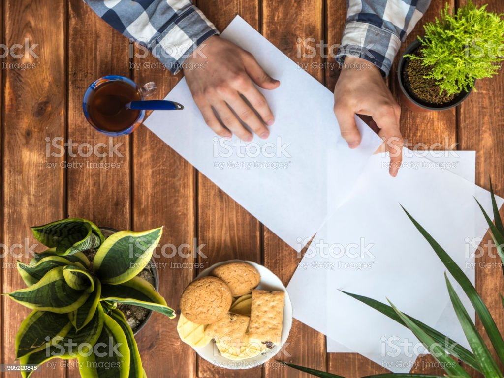 hands making handmade paper works on a wooden table royalty-free stock photo
